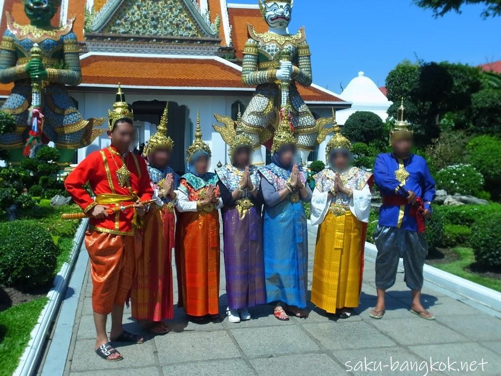 ワット・アルンでタイの伝統衣装を身にまといヤック像の前で写真を撮る人々