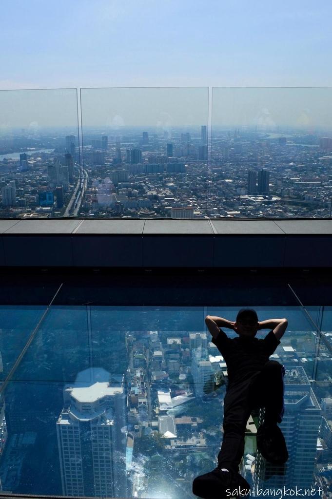 マハナコン展望台のガラス板の上で寝転ぶ人