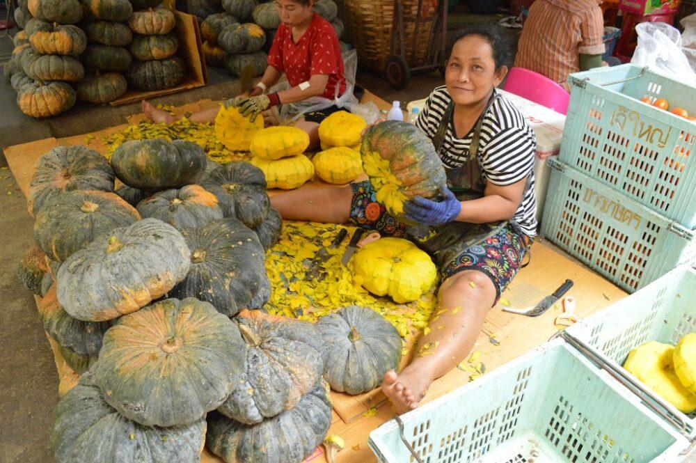 巨大なかぼちゃを剥く市場の女性